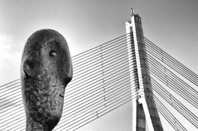 """""""Él y el Puente"""" (He and the Bridge) por Oleg Dashkov en Riga, Letonia. """"'Riga's Tower Counter' se mantiene durante cualquier temporada de lluvias o sol, mojado o seco. Me pregunto si estará distraído por la belleza del puente de cable...""""."""